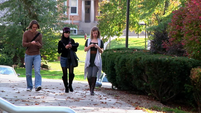 Students texting while walking on campus. - HD stock footage clip
