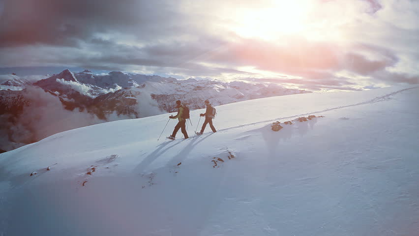 hiking in the snow. hikers walking. foot feet steeps. snow winter landscape. sports recreation activity. holiday vacation tourism. people persons male silhouette. fly over. aerial