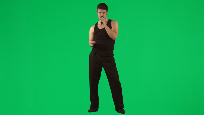 Man singing with a microphone against green screen - HD stock footage clip
