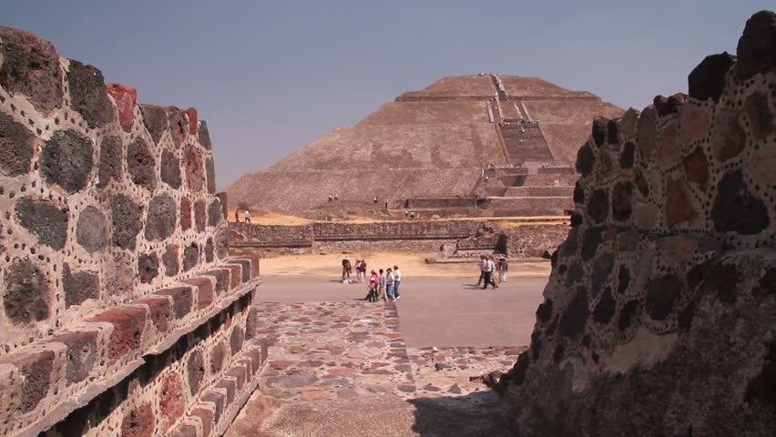 Old stones of the ancient Mayan pyramids in Mexico. Dolly shot of the pyramid of the sun through the old stones in the foreground