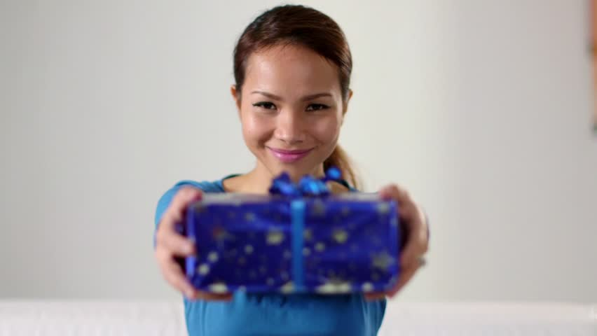 Young people with gift box, asian woman showing present to the camera and smiling