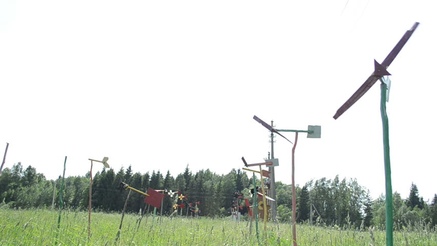 pinwheels collection spin in wind. Windmills made of old car and wood parts in garden high grass. - HD stock video clip