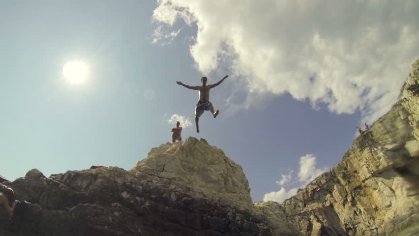 SLOW MOTION: Young man jumps into the ocean - HD stock video clip