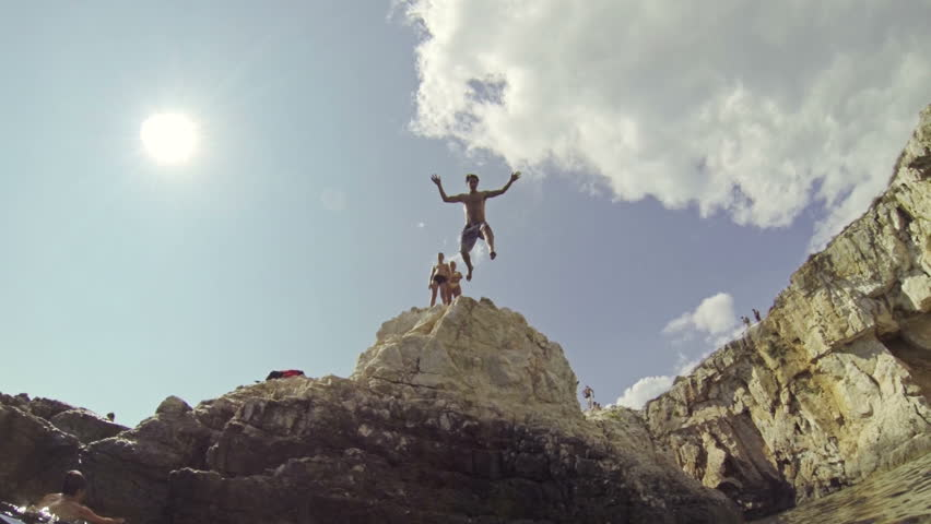 SLOW MOTION: Man jumping of the cliff into the ocean - HD stock footage clip