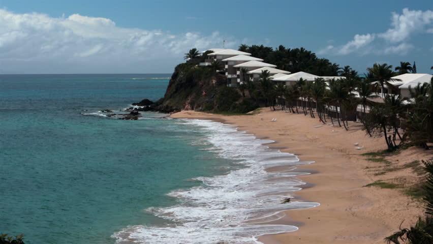 Antigua Island beach resort surf palm trees. Family and couple beach fun and recreation. Caribbean Ocean warm outdoor activity. Beautiful sand shell seashore. Tropical environment tourist destination.