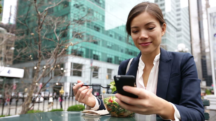 Young business woman eating salad on lunch break in City Park living healthy lifestyle working on smart phone. Happy smiling multiracial young businesswoman, Bryant Park, Manhattan, New York City, USA - HD stock footage clip
