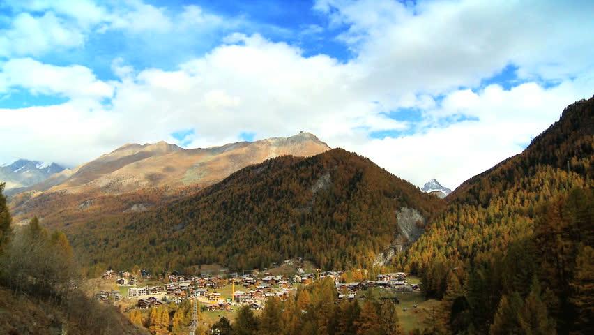 Time-lapse clouds over Zermatt village in alpine meadow at the base of Matterhorn, Switzerland - HD stock video clip