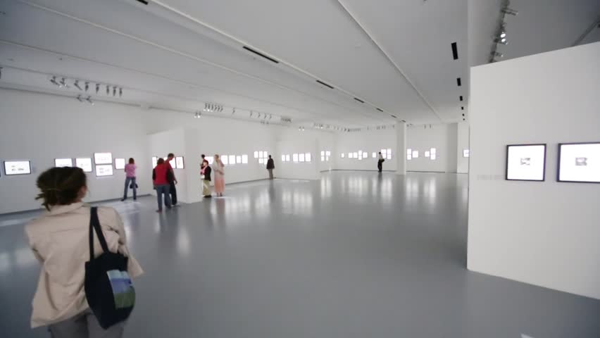 People walk on photo exhibition in large grey gallery