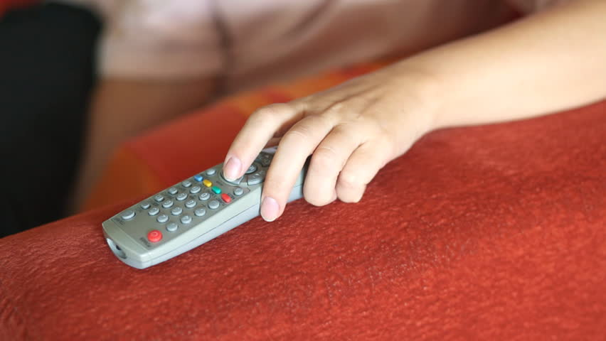 HD 1080 static:  female human hand holding remote TV control, changing channels