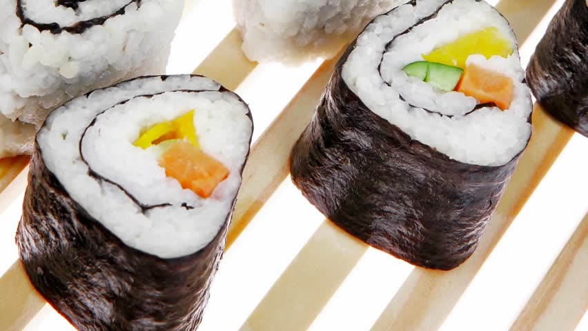 Maki Rolls and California rolls made of fresh raw Salmon Tuna and Eel with Cream Cheese and Avocado . Isolated . on wooden grid . Maki Sushi and Nigiri 1920x1080 intro motion slow hidef hd