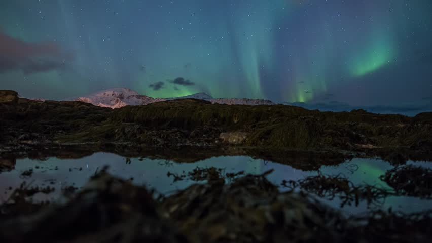 Aurora Borealis (Northern lights) Panning timelapse on rock pools at Norway beach