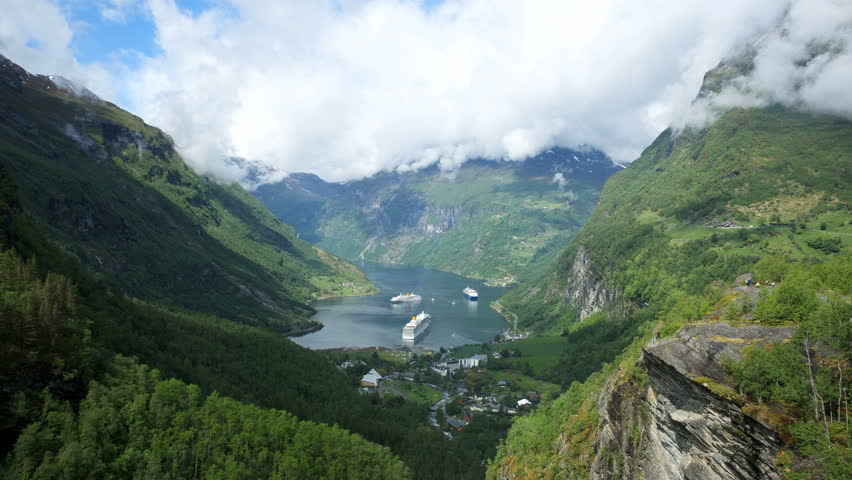4K view of Geiranger cruise ships wild steep mountains waterfalls and clouds in a amazing scenery