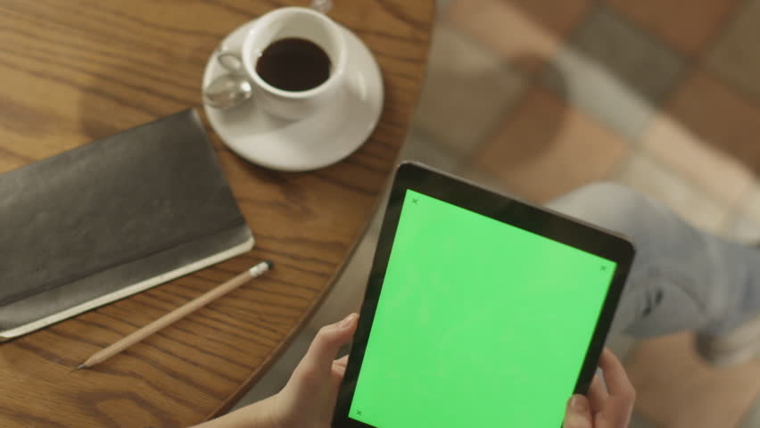 Girl Using Tablet PC with Green Screen. Shot on RED Digital Cinema Camera in 4K (ultra-high definition (UHD)), so you can easily crop, rotate and zoom. Easy for tracking and keying. ProRes HQ codec.