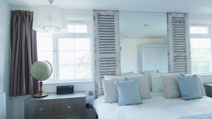 Interior view of elegant bedroom with en suite bathroom in a stylish beachside home with lots of natural light. No people.