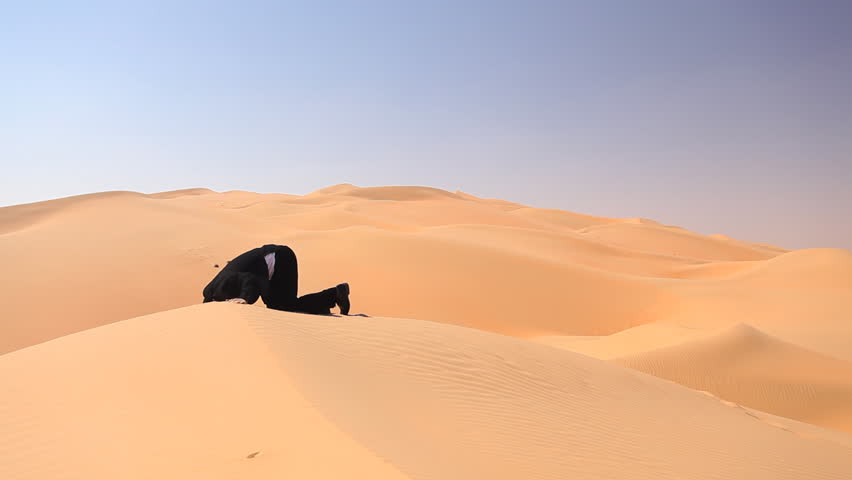 businessman sticking his head into the sand in desert - HD stock video clip