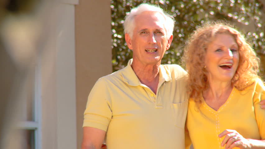Attractive senior couple excited about their retirement real estate property move - HD stock footage clip