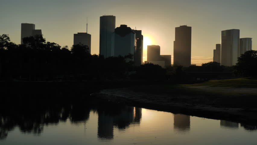 Houston, Texas - November 20, 2013 - Dawn time lapse of the Houston skyline silhouetted against the rising sun and reflected on the Buffalo Bayou.  Shot at 4k resolution.