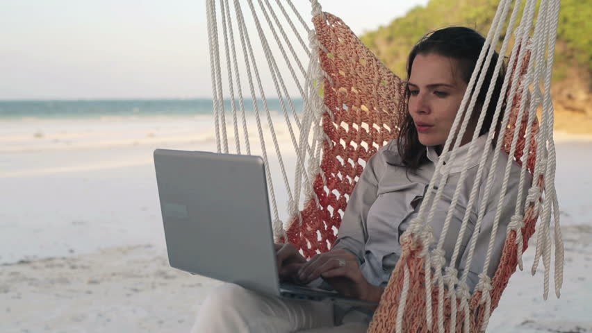 Businesswoman working on laptop on hammock, on exotic beach