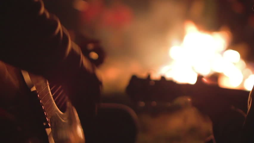 Playing the guitar at campfire. - HD stock footage clip