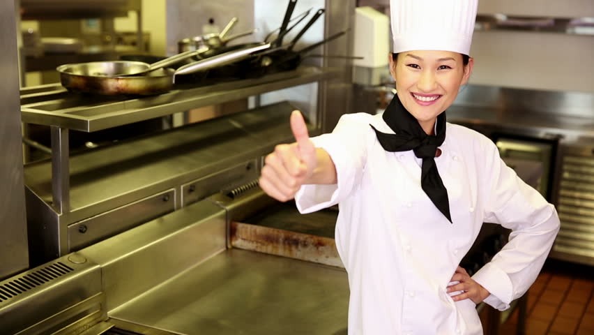 Happy chef smiling at camera beside the stove in commercial kitchen - HD stock footage clip