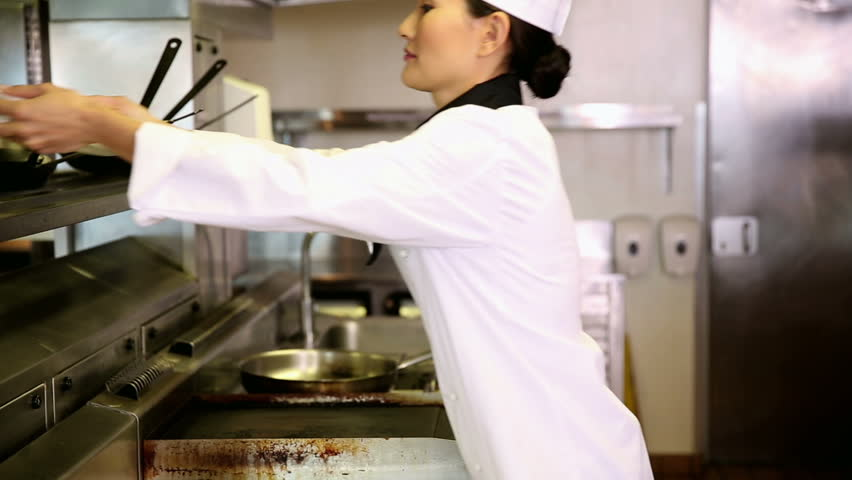 Asian chef putting away stack of plates in commercial kitchen - HD stock footage clip