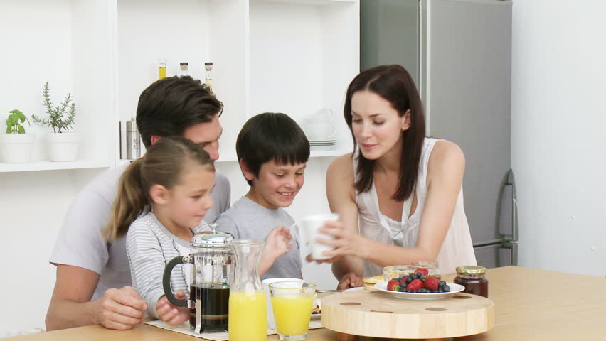 Happy young family having breakfast in the kitchen. Nutritive meal. Footage in high definition - HD stock footage clip