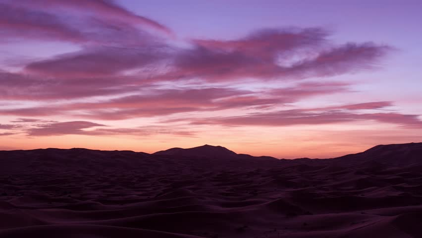 Timelapse of the vibrant sunrise over the Sahara Desert in the dunes between Morocco and Algeria.