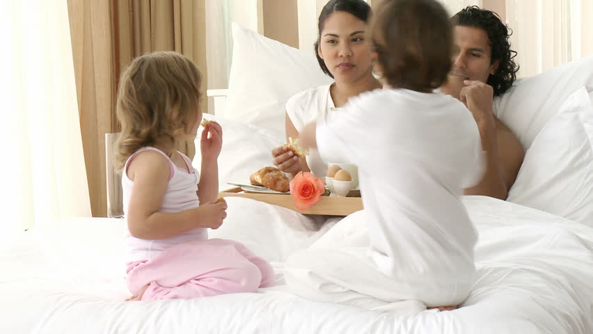 Happy family having breakfast in bed. Footage in high definition - HD stock footage clip