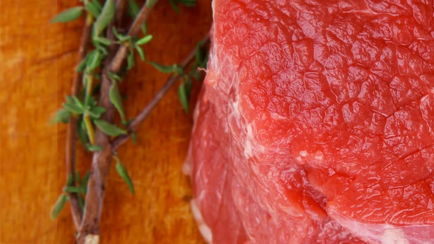 raw red meat : two fresh beef fillet chops with small thyme twig on wooden plate . 1920x1080 intro motion slow hidef hd