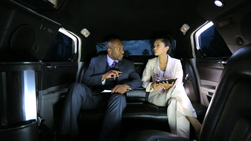 Corporate multi ethnic business leaders using wireless tablet smart phone technology while being chauffeur driven in luxury limousine - Business Leaders Wireless Tablet Smart Phone Limousine