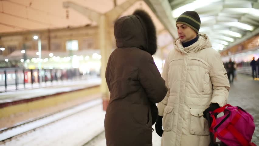 Man and woman look for something in handbag and go away on railway station