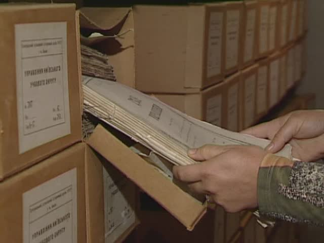 Old archive documents on shelves and in the hands