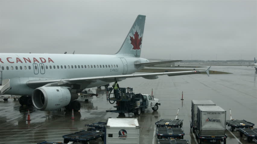 DALLAS, TEXAS - JAN 2014: Dallas Airport aircraft gate refuel rain. Air Canada. Storm. Commercial airline aircraft prepare for next flight by refueling and loading baggage. Workers busy bad weather.