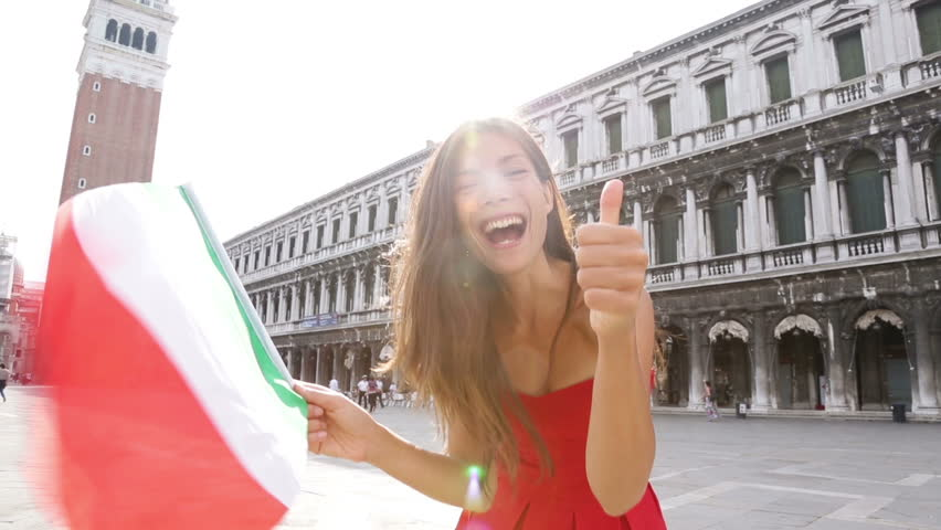 Woman waving Italian flag happy in Venice, Italy. Smiling cheerful multiracial girl having fun on San Marco Square, Venice, Italy. Caucasian Asian model giving thumbs up looking at camera.