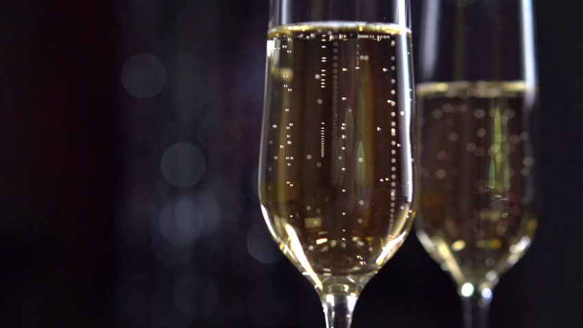 Champagne. Two Flutes with Sparkling Champagne over Holiday Bokeh Blinking Background. Full HD 1080p video footage. Slow motion