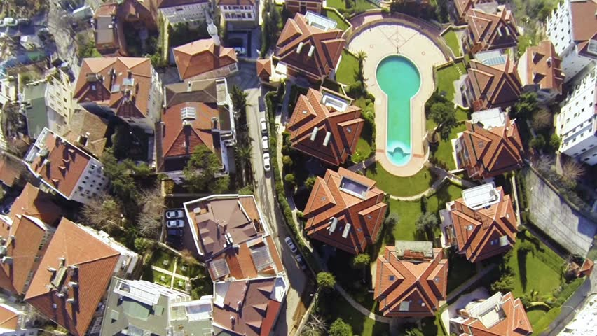 Fly over, looking down on a residential housing community in Istanbul. Birds eye view of luxury houses and the swimming pool at Uskudar district.
