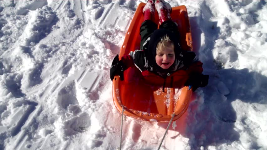 toddler boy goes for a toboggan ride across a snow field (loopable) - HD stock footage clip