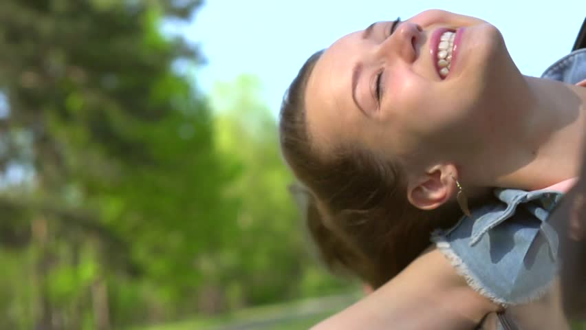 Happy Teenage Girl sitting in car passenger seat and looking out window on sunny day. Vacation concept. Full HD video footage 1080p. Slow motion 240 fps