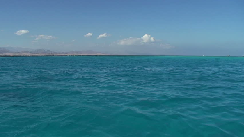 Turquoise water with desert coastline, blue sky and sparse clouds in the background. Gulf of Aquaba, Red Sea, Egypt. - HD stock video clip