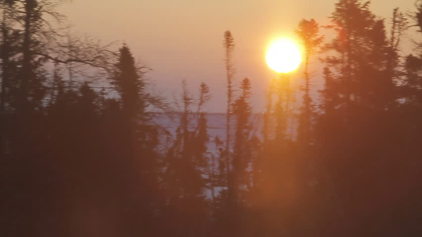 Sunrise over tundra out of train through trees