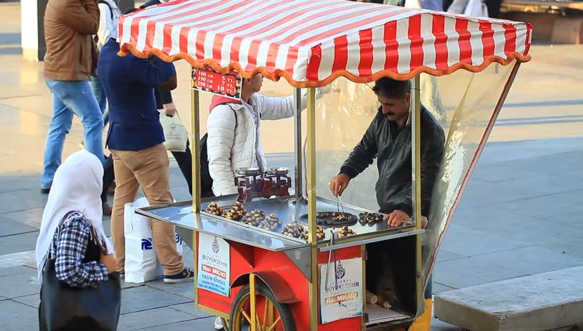 ISTANBUL, TURKEY - OCTOBER 14, 2012: Chestnut roast on street vendor food cart at Eminonu. Street vendors are omnipresent on Istanbul streets. Roasted chestnuts are a seasonal treat sold.