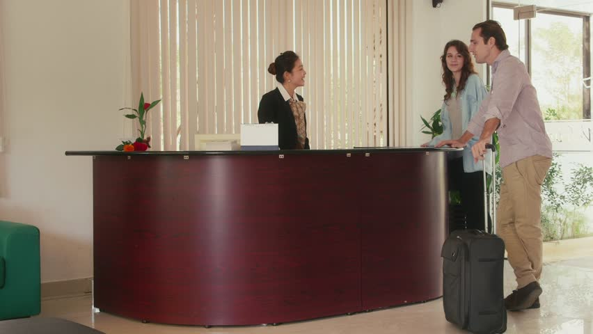 Young people and leisure, lifestyle and fun, travel and vacations, man and woman on holiday. Happy married couple arriving at hotel lobby desk, talking to receptionist for assistance. 1of12