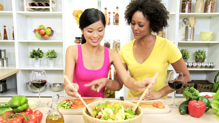 Female Flat Mates Kitchen Slicing Fresh Salad Vegetables - African American Asian Chinese female friends home kitchen slicing delicious market fresh peppers cucumber healthy living meal