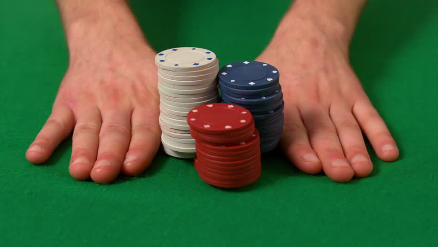 Man pushing casino chips over in slow motion
