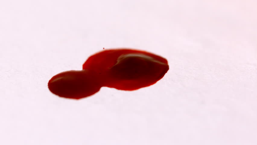 Blood dropping on white surface in slow motion