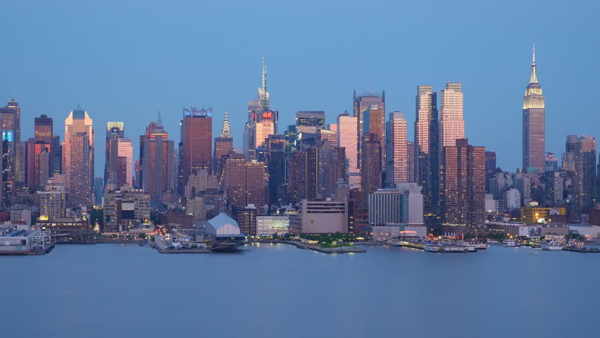 Building lights are illuminated during early twilight as the western sky is still reflected off the windows of the mid-town Manhattan skyline over the Hudson River just after sunset in New York City.