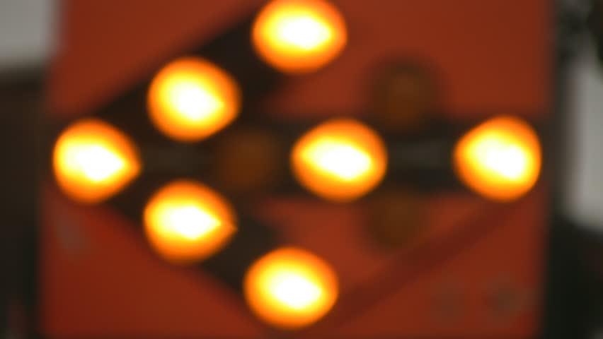 Flashing orange arrow.  Defocused orange roadworks sign points left. Two shots.  - HD stock footage clip