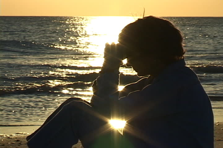Mature woman sits on the beach praying with hands folded against head. Sunlight sparkles on the water in the background. Shot on miniDV from a tripod. - SD stock footage clip