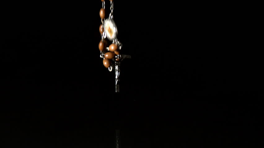 Crucifix falling on black background in slow motion