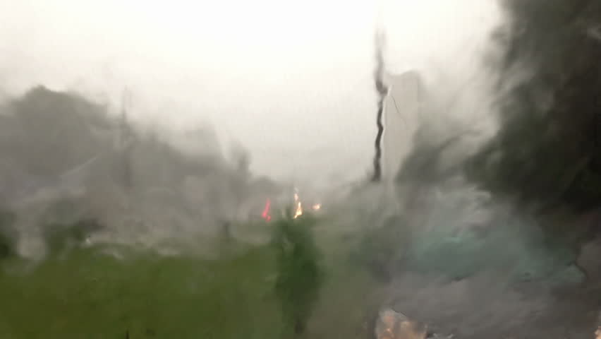 Summer rain in the city. Shot through the windscreen with heating threads and wipers. - HD stock footage clip